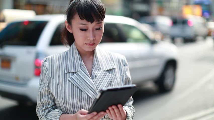 Asian business woman using iPad tablet pc computer reading ebook ibook | Shutterstock HD Video #4898792