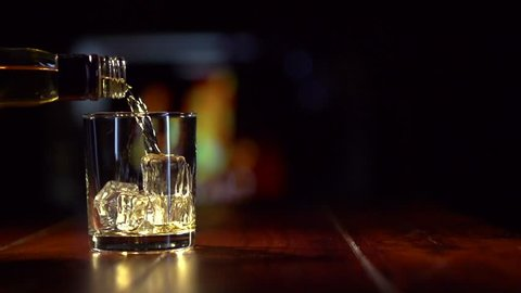 Pouring a scotch whiskey on the rocks. Slow Motion Shot