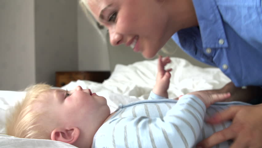 Mother kissing and shaking adorable baby boy on bed