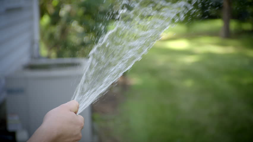 Stream of  water spraying from garden hose. 240 fps slow-motion.