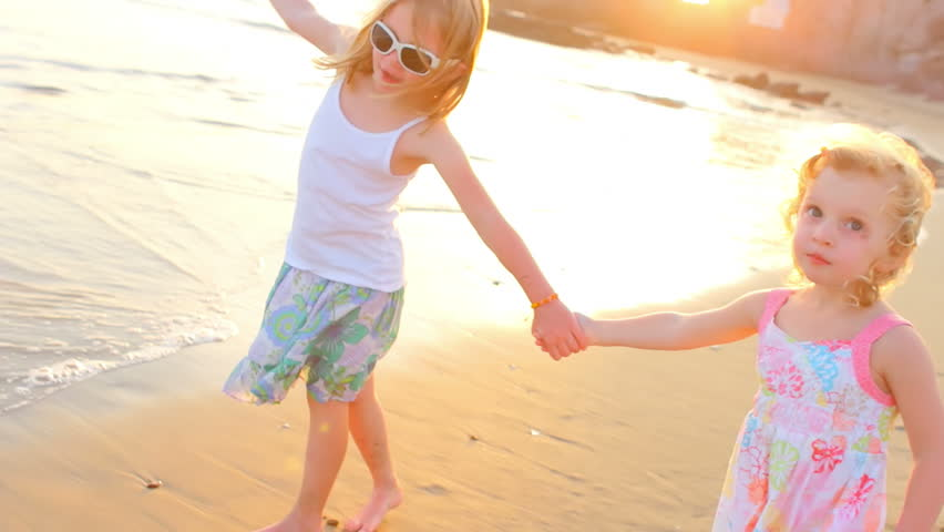 Two young girls hold hands and play at the beach, on the shore line