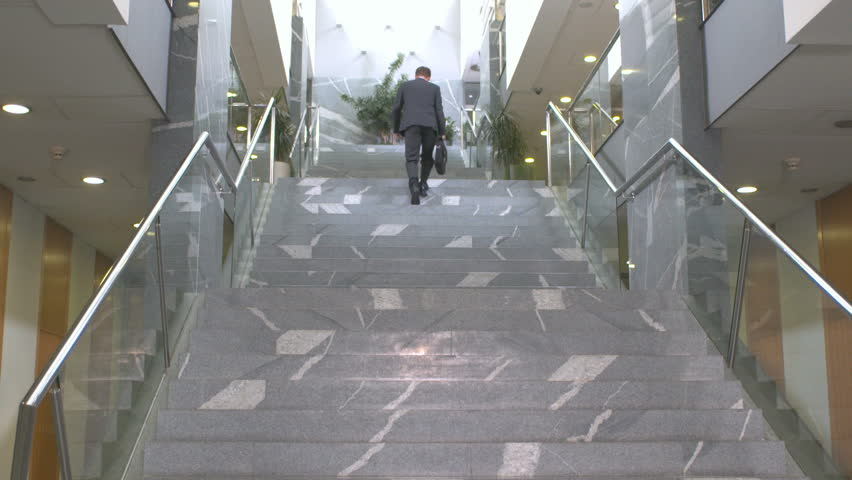Edited Shot Of A Successful Businessman Walking Up The Stairs Inside Business