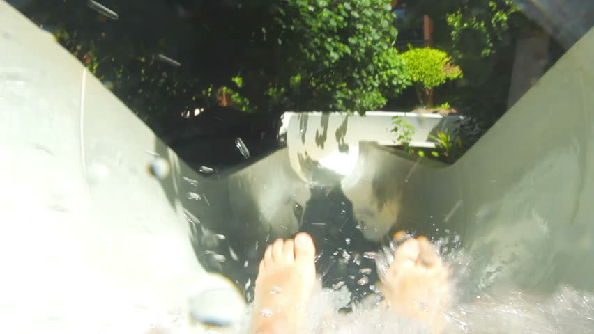 First person view of someone riding down a water slide and into a pool | Shutterstock HD Video #4941335