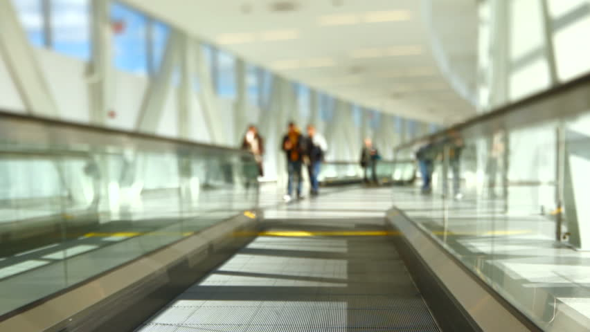 Airport travelers walking by while on moving walkway.