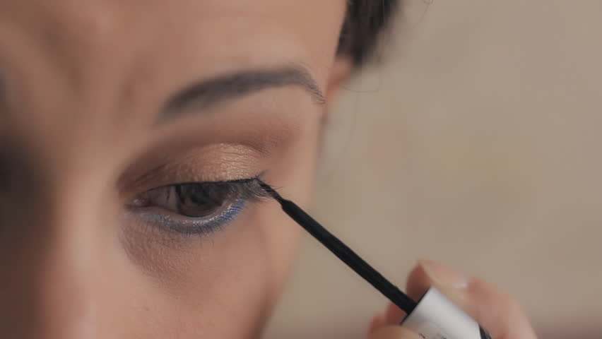 Smiling attractive woman applying make up on her eyebrows