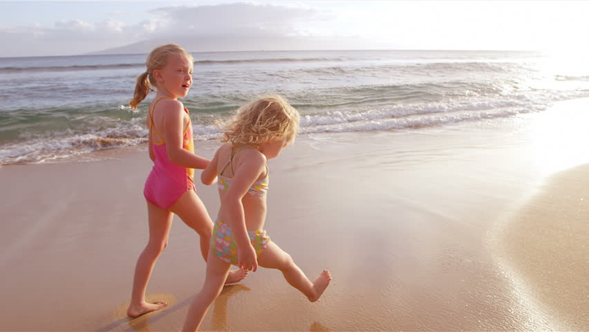 Two cute little girls walk down the beach in the waves on a beautiful day while the sun sets. Medium shot.