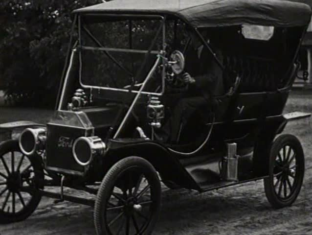 1920s - Henry Ford poses in one of his first Model T cars and other later models.