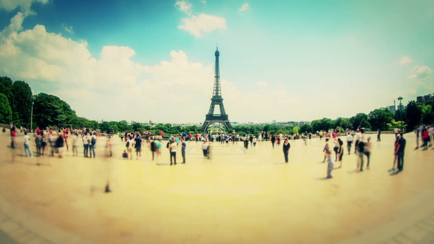 Zooming fisheye pedestrian traffic time lapse with Eiffel Tower in background.