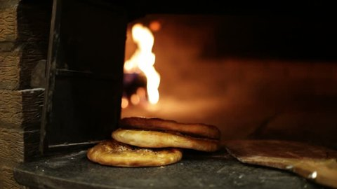 Turkish bread called Pide on the mouth of the oven where it has been cooked