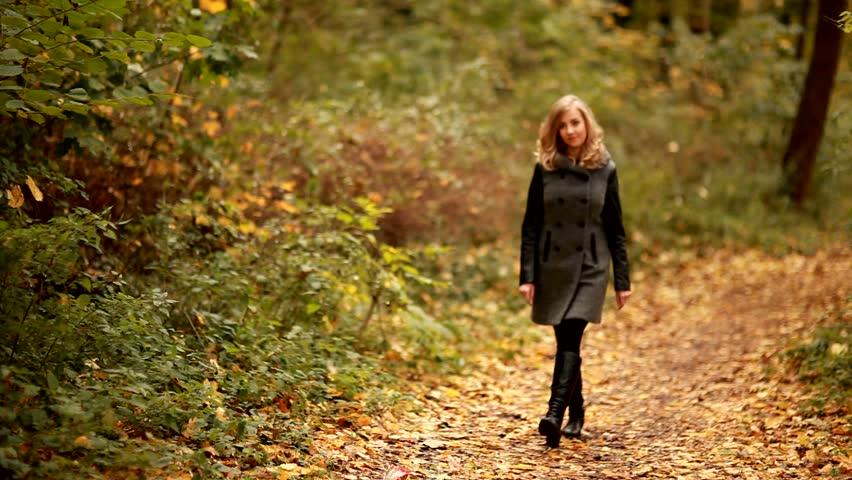 stock video clip of blond elegant woman walking in park