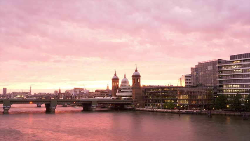 Sunset over the City of London. Thames River and office buildings, with Blackfriar's Bridge in the center. A passenger boat passes by. | Shutterstock HD Video #5000492