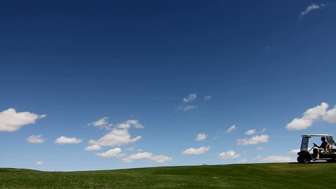 Golf cart driver, silhouetted, drives on golf course road, surrounded by rich green turf, blue sky, clouds background. 1080p