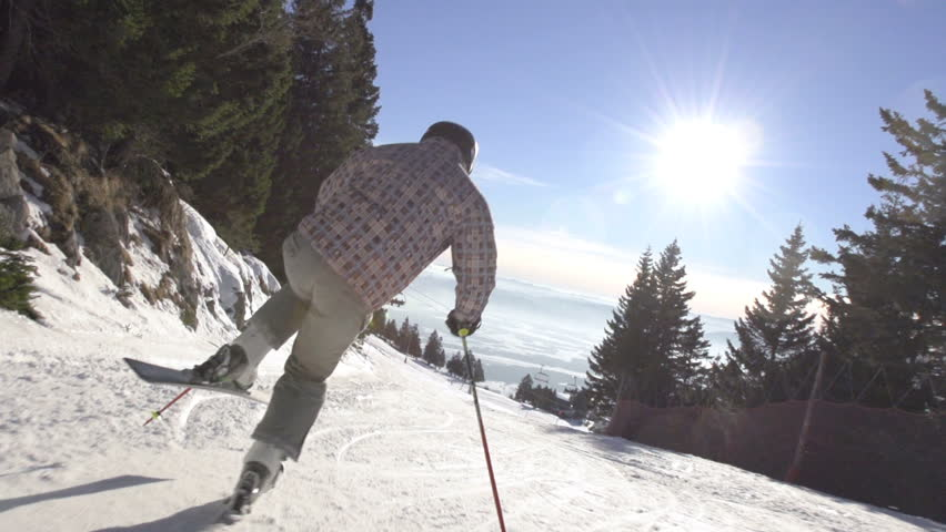 Slow Motion Rear View Of Skier Carving Down Steep Slope On A Sunny Winter Day.