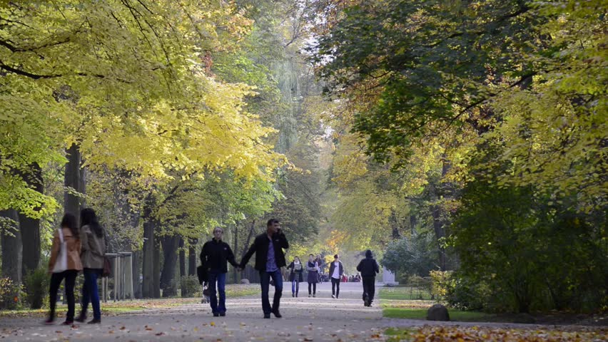 WARSAW, POLAND - OCTOBER 11: Undefined pedestrian walking in Lazienki Krolewskie Park on October 11, 2013 in Warsaw, Poland. ?azienki Park is  the largest park in Warsaw.