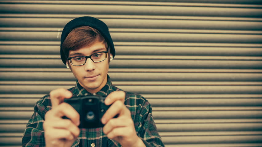 Hipster taking pictures with old vintage camera in grunge color correction