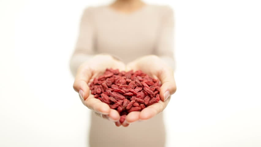 Goji berries - dried Goji berry heap / wolfberries. Superfoods - woman showing dried goji berries. Heap of organic healthy wolfberry superfood.