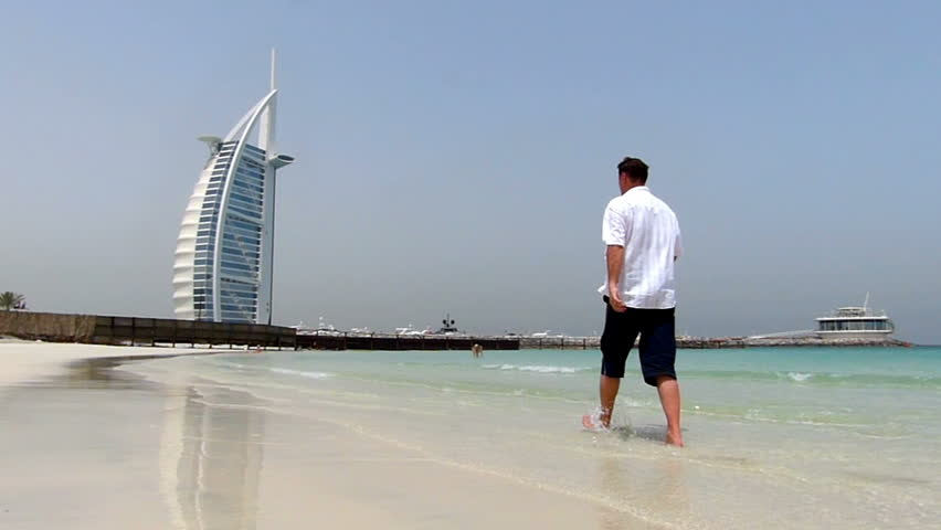 Man walking along the beach in front and the Burj Al Arab hotel, high speed camera, slow motion