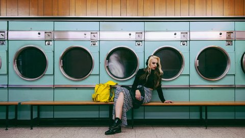 Woman waiting for laundry at launderette cinemagraph seamless loop