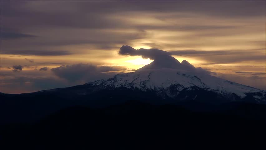 Mt Hood at Sunrise - CLOSE. The clouds swirl above Mt. Hood as the sunrises behind. Beautiful golden sky