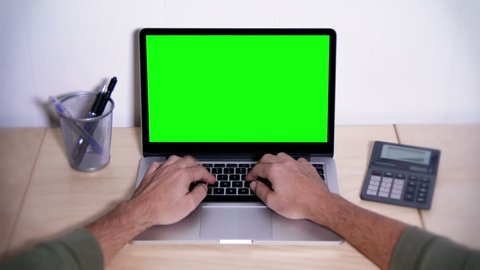 A man types on a laptop on his desk.  Green screen for your custom screen content.