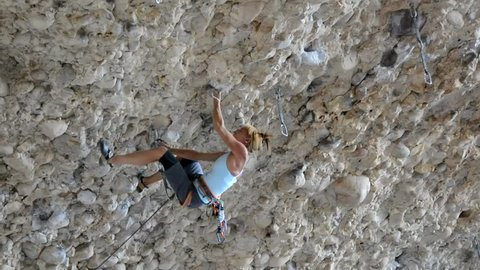 Female Rock Climber on Steep Conglomerate. Female rock climber on The Great Feast (5.13c) in Maple Canyon, UT.