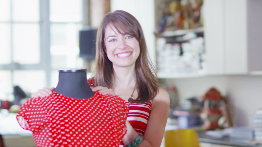 Portrait of a young female fashion designer standing with one of her designs.