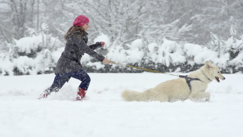 Slow Motion Of A Young Woman Running Through Fresh Snow With Her Beautiful White