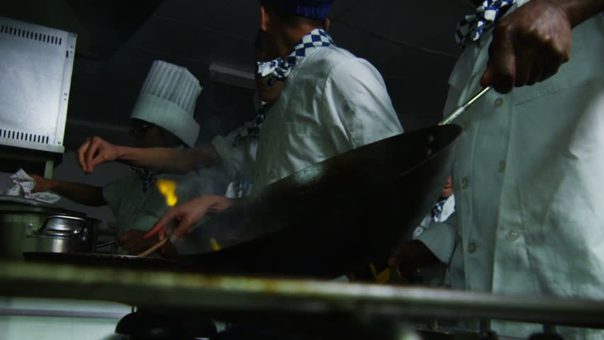 Professional chef in a commercial kitchen cooking flambe style. In slow motion.