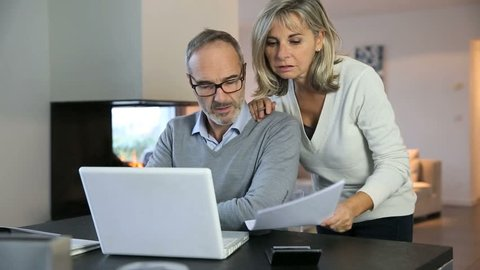 Senior couple at home using internet on laptop computer