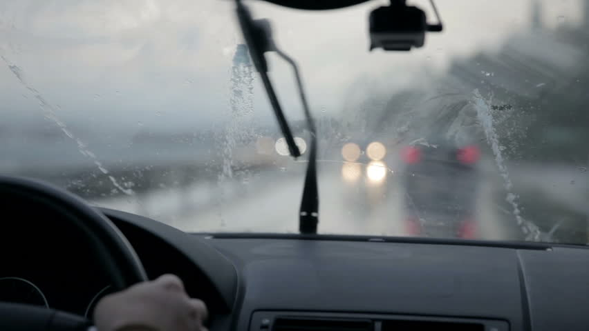 Windscreen wipers cleaning windshield glass on rainy dawn
