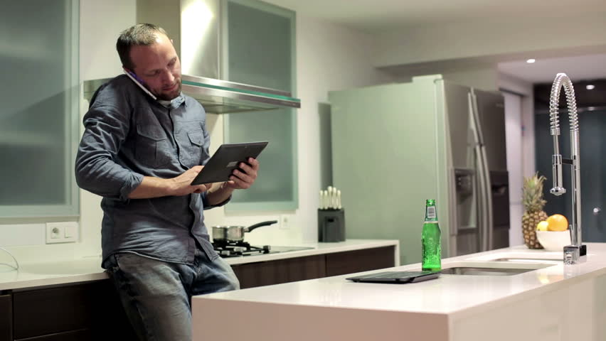 Young man with tablet computer talking on cellphone in kitchen