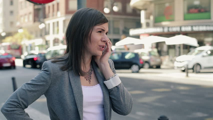 Young attractive businesswoman talking on cellphone by the street