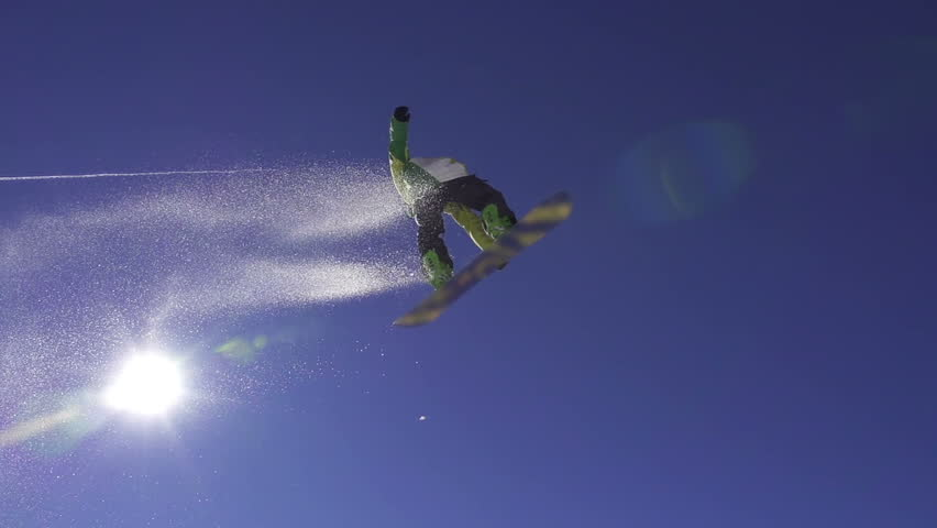 SLOW MOTION: Snowboarder jumps over kicker, low angle view