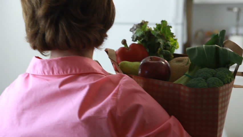 A woman carrying a grocery bag, places the bag on her kitchen counter and proceeds to take from the bag an assortment of fruits and vegetables. (Shoulder mount)