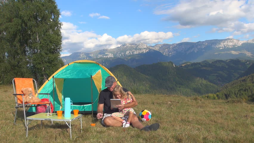 Man Father With Child Use Playing Tablet In Mountains Trip In C&ing Family On Grass By Tent People Traveling In Vacation Summer View Gadgets Stock ... & Man Father With Child Use Playing Tablet In Mountains Trip In ...