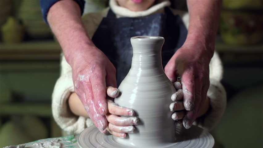 Close-up of a little girl learning how to model clay, her tutor helping