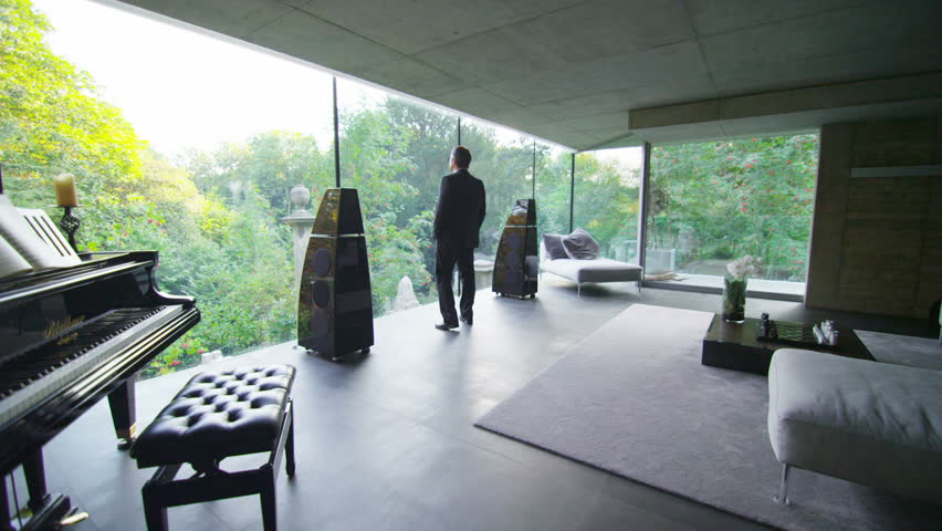 Businessman in luxury contemporary home goes to the window to look at the view. In slow motion. #5234639