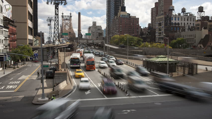 NEW YORK - OCTOBER 18: (Time-lapse) Mid-day traffic enters Manhattan from Queens on the Queensboro Bridge as the Roosevelt Island Tram leaves the station on October 18, 2012 in New York.
