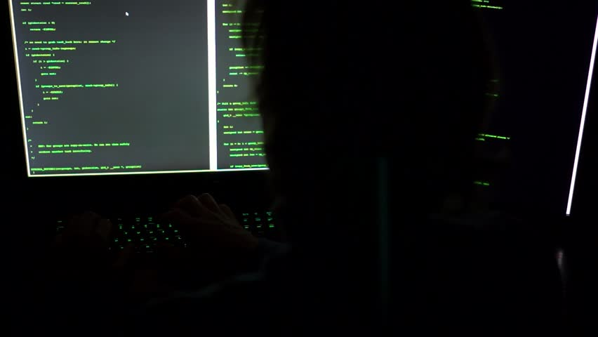A hacker types green code in darkness on multiple screens.