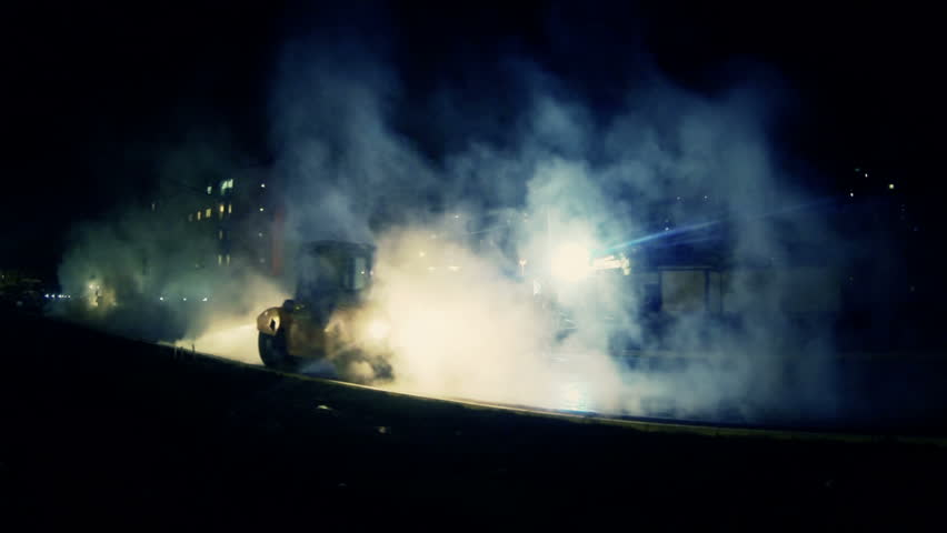 Heavy road machinery. Night steamy work