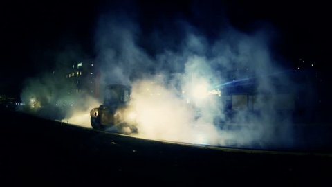 Heavy road machinery. Night steamy work