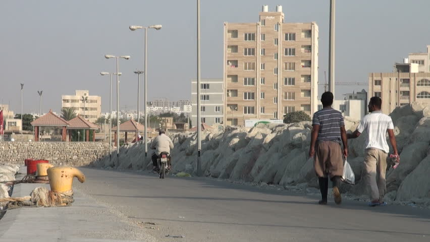 BANDAR ABBAS, IRAN - 31 OCTOBER 2013: Two fishermen are walking home, after a night at sea, in the coastal city of Bandar Abbas, Iran