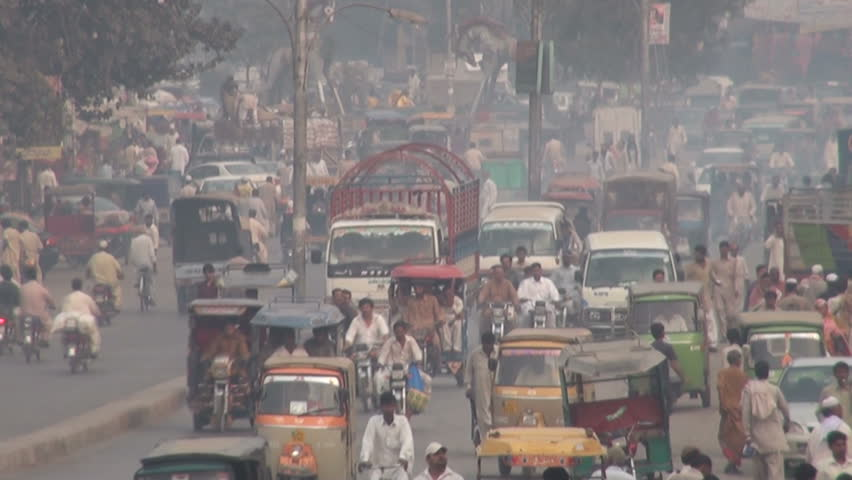 LAHORE, PAKISTAN - 24 OCTOBER 2010: Traffic drives through the streets of Lahore, leaving a trail of smog
