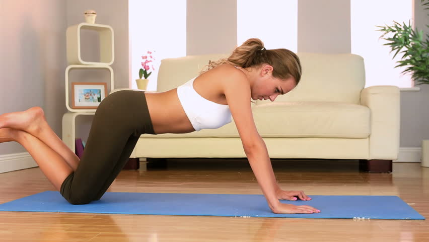 Sporty brunette doing push ups at home in bright living room