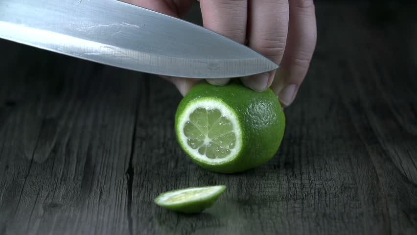 Stock Video Clip of Cutting up a lime with kitchen knife ...