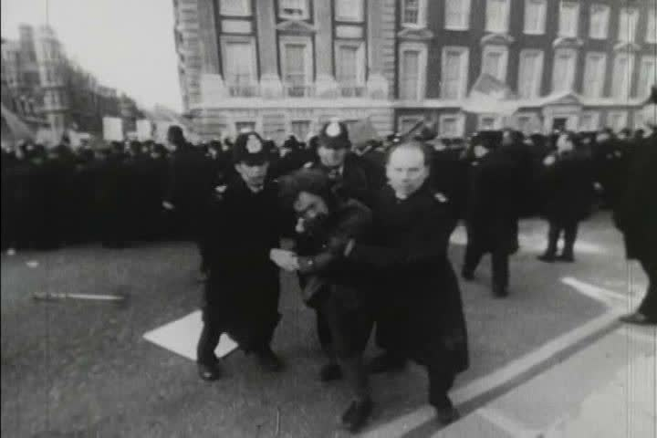 1970s black and white footage of people protesting the Vietnam War and being contained by police in London, England
