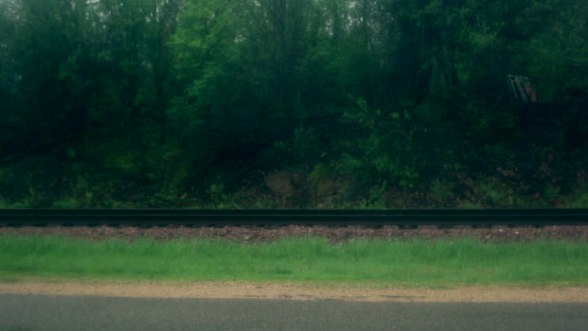Young couple (man and woman), playfully running along a trail by a railroad track in the rain. Boy with umbrella runs from girl as she chases after him