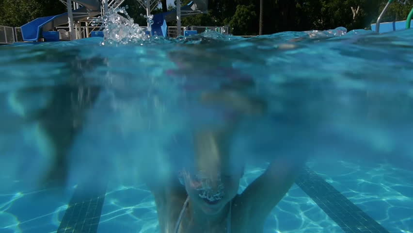 Girl diving in swimming pool. Slow Motion. Perfect for videos about: swimming, pools, summer fun, vacation, getaways, underwater footage, kids, beating the heat, and exercise.