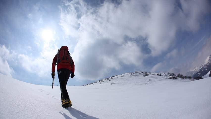 Mountaineer walking uphill along a snowy slope. Rear view. Western Alps, Europe. HD1080P | Shutterstock HD Video #5364752