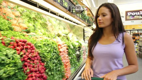 Woman looking at produce in grocery store. Professional Hispanic model. Shot in a Riverside, California market with permission in June, 2011.